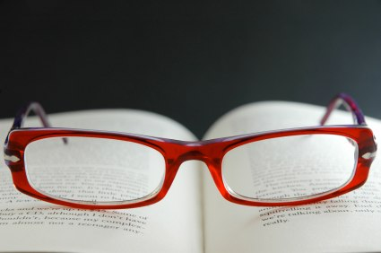A pair of red spectacles on top of an open book